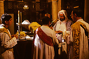 "Old Cairo. St Barbara Coptyc church, holy mass. Built on the ruins of a 5th century church the present church dates to the 12th century. The fine wooden iconostasis with inlays of ivory is from the 13th century. Coptics, Greek Orthodox, Syrians, only few components of the fragmented galaxy of the ""living stones"" as often are defined the oriental christian churches, are the protagonists of a frequently forgotten world that currently menaces to die in the same places in which Christianity born. Rituals and stories similar to legends lost in time survive intact and in these places regain the strenght of a living reality."