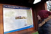 Middle aged woman with red hat and black jacket looks at Annandale Way Interpretation Panel, Moffat, Annandale Way