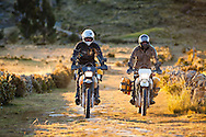 Two adventure motorcyclists ride an Inca road near the village of Sampaya in Bolivia's Copacabana Peninsula, next to Lake Titicaca.