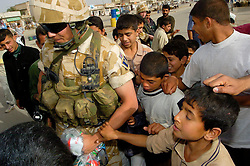 Soldier from the East and West Riding Regiment, Territorial Army, wearing desert camouflage, Kevlar helmet and body armor, carrying SA80 assault rifle which are fitted with SUSAT sights on foot patrol through the streets of Basra during Op Telic in March 2005 hands out sweets and toys to local children