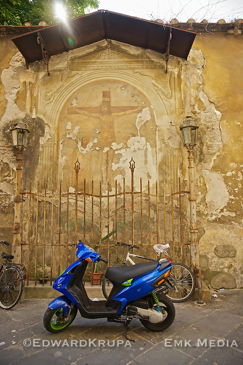 Scooters, bikes, Jesus Christ..Lucca, Tuscany, Italy.