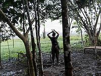 A female member of the FARC rebels fixes her hair while on guard duty in a camp in the remote Putumayo region of Colombia, on December 9, 2016. (Photo/Scott Dalton)