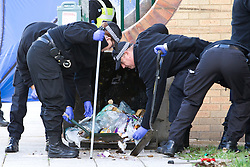 © Licensed to London News Pictures. 06/10/2012. Walsall , UK .  Police search through rubbish outside the block of flats . Police and forensic examiners investigate after two bodies were found at a block of flats . A woman was found inside a flat in Holly Court , Acacia Avenue , Walsall and a man was found dead outside the block . Photo credit : Joel Goodman/LNP