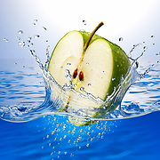 Apple half splashing into water Ray Massey is an established, award winning, UK professional  photographer, shooting creative advertising and editorial images from his stunning studio in a converted church in Camden Town, London NW1. Ray Massey specialises in drinks and liquids, still life and hands, product, gymnastics, special effects (sfx) and location photography. He is particularly known for dynamic high speed action shots of pours, bubbles, splashes and explosions in beers, champagnes, sodas, cocktails and beverages of all descriptions, as well as perfumes, paint, ink, water – even ice! Ray Massey works throughout the world with advertising agencies, designers, design groups, PR companies and directly with clients. He regularly manages the entire creative process, including post-production composition, manipulation and retouching, working with his team of retouchers to produce final images ready for publication.