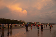 Lots of people on the busy Laboni Beach at sunset in Cox Bazar, Chittagong Division, Bangladesh, Asia. Beachfront buildings of the city can be seen in the background. Sunlight is reflected in the wet sand on the beach.  (photo by Andrew Aitchison / In pictures via Getty Images)