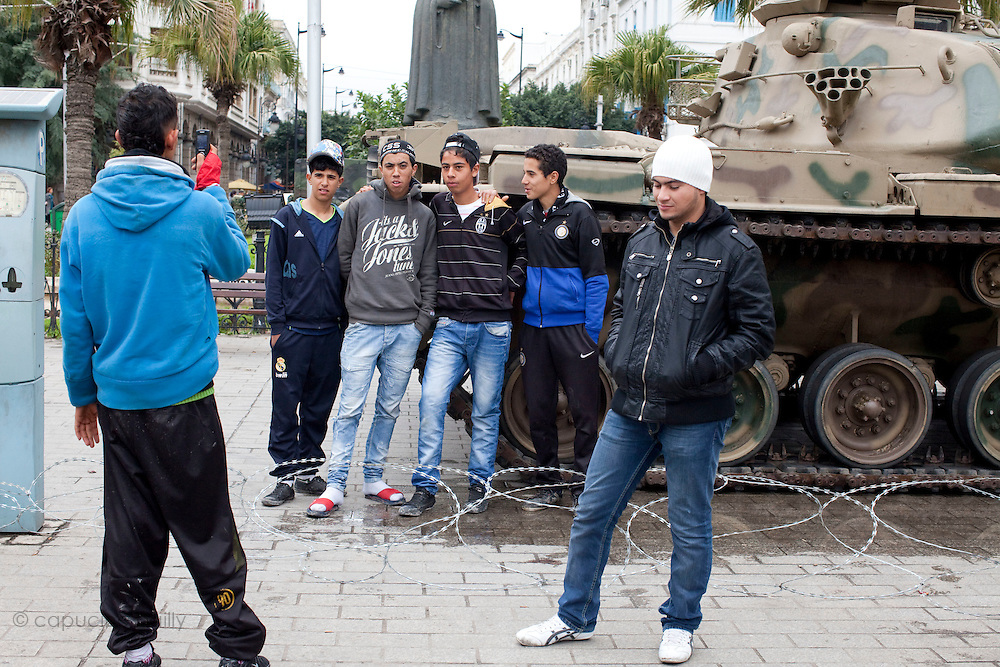Tunis, Tunisia. January 27th 2011.People ask to be photographed in front of the army tank..A daily life scene outside the protests places, thirteen days after the ousted president Zine El Abidine Ben Ali fled the country.....