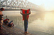 Dawn bather covers his face with red cloth as sun rises over the Hooghly River, KolIkata. It is dawn in Calcutta, West Bengal, India and on the West bank of the Hooghly River the sun is rising from across the Howrah Bridge. Six bathers are either drying themselves after washing in the river, or are undressing to do so. It is a scene of inner-peace, a tranquillity surrounded by the chaotic pace of Indian life in this city. The engineering of the bridge stretches across the water towards the city beyond. The bridge is one of three on the Hooghly River and is a famous symbol of Kolkata and West Bengal. Bearing the daily weight of approximately 150,000 vehicles and 4,000,000 pedestrians. It is one of the longest bridges of its type in the world. The Hooghly River is an approximately 260 km long distributary of the Ganges River.