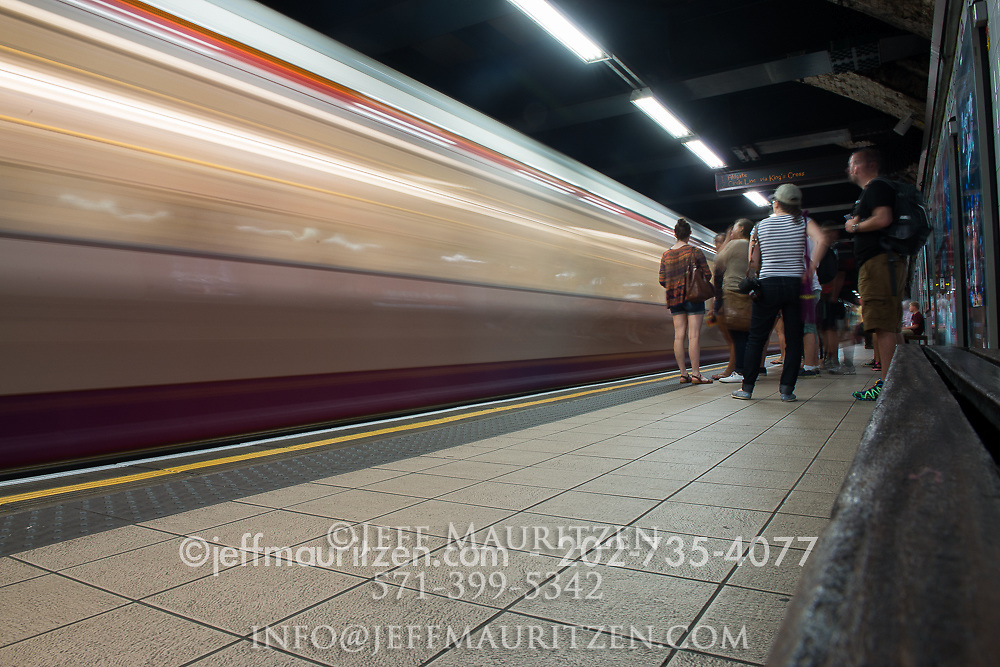 A London Underground train travels past in a blur of motion.