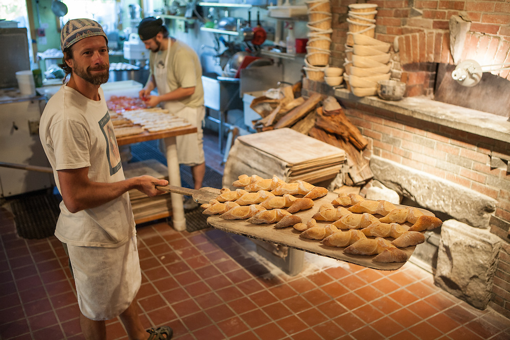 Jamestown, RI - 7 May 2007. Andrea Colognese of The Village Hearth Bakery and Cafe, putting loaves of pain d'epi fresh from the oven onto cooling racks.