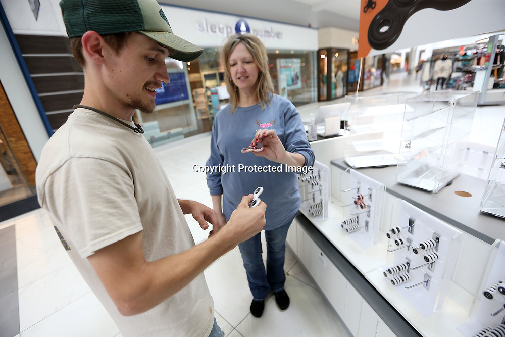 Martha Mitchell, right, an employee with Sunny Shades, talks with Tyler Jordan, of Bruce, about the Fidget Spinners at the Fidget kiosk inside the Mall at Barnes Corssing.