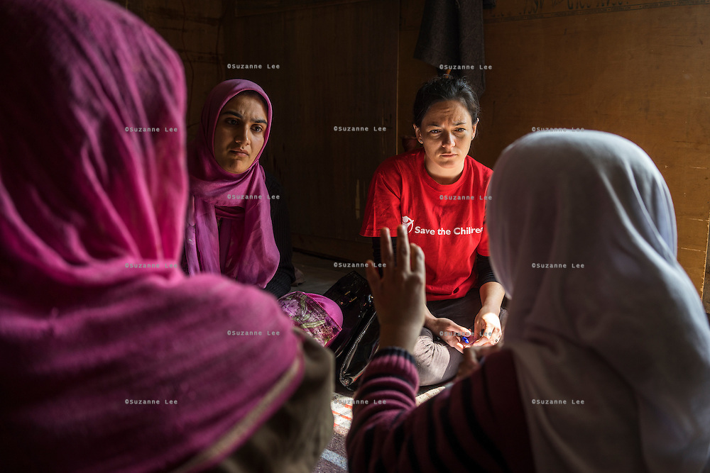 (Alison Griffin to fill in names) Save the Children team members talk to flood victims about their losses and the devastation for the floods in Abikarpora village on the Dal Lake, Srinagar, Jammu and Kashmir, India, on 25th March 2015. Since the flood, she has been widowed, and is left with four young children and no home. Her family now lives in a temporary shelter built using the emergency shelter kit, and continues their recovery with the help of relief kits such as education kit, food basket, hygiene kit and non-food items from Save the Children. Photo by Suzanne Lee for Save the Children