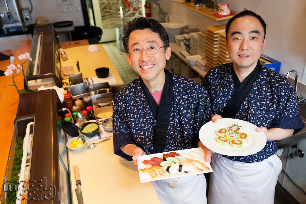 Happy chefs with prepared Asian cuisines in restaurant
