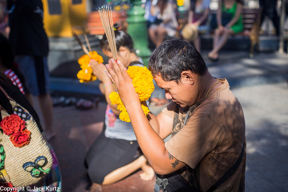 """01 JUNE 2014 - BANGKOK, THAILAND:  People pray at Erawan Shrine in Ratchaprasong before expected protests started. The Thai army seized power in a coup that unseated a democratically elected government on May 22. Since then there have been sporadic protests against the coup. The protests Sunday were the largest in several days and seemed to be spontaneous """"flash mobs"""" that appeared at shopping centers in Bangkok and then broke up when soldiers arrived. Protest against the coup is illegal and the junta has threatened to arrest anyone who protests the coup. There was a massive security operation in Bangkok Sunday that shut down several shopping areas to prevent the protests but protestors went to malls that had no military presence.   PHOTO BY JACK KURTZ"""