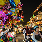 Busy traffic on bicycles and scooters at night in Hanoi's Old Quarter. At left a balloon vendor sells his wares.