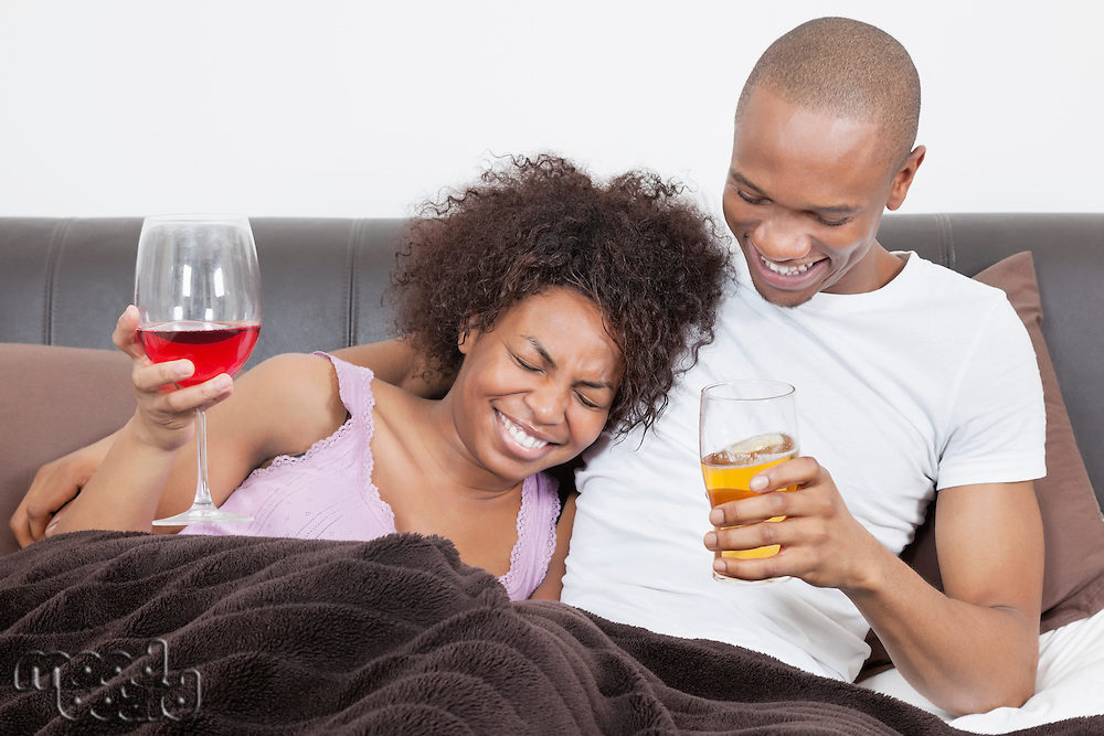 Young African American couple enjoying drinks together in bed