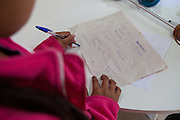 A young girl practices her writing and spelling at the community library, Biblioteca Comunitaria do Arquipelago, Porte Alegre, Brazil. <br /> <br /> Cirandar is working in partnership with  C&A and C&A Instituto to implement a network of Community Libraries in eight communities of Porto Alegre.