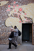 Muslim couple walk beneath a world map on a bakery business hoarding.