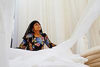 Inde, Rajasthan, Usine de Sari, Les tissus sechent en plein air. Ramassage des tissus secs par des femmes et des enfants avant le repassage. Les tissus pendent sur des barres de bambou. Les rouleaux de tissus mesurent environ 800 m de long. . // India, Rajasthan, Sari Factory, Textile are dried in the open air. Collecting of dry textile  are folded by women and children. The textiles are hung to dry on bamboo rods. The long bands of textiles are about 800 metre in length.