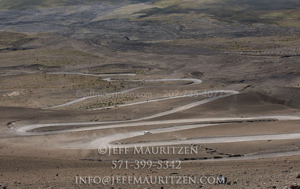 A car drives down the switchback road that leads up to Cotopaxi volcano in Ecuador.