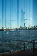 Liberty Island, NY - 9 January 2020. The southern end of Manhattan seen from inside the Statue of Liberty Museum, with Ellis Island on the left, and a reflection of the Statue of Liberty in the window.