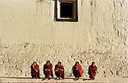 November 2006 - Shangarila, China - At Songzhalin Monastery five Tibetan Buddhist monks squat on a ledge in the morning sun.<br /> Photo credit: Luke Duggleby