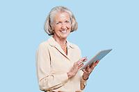 Portrait of senior woman using tablet PC against blue background