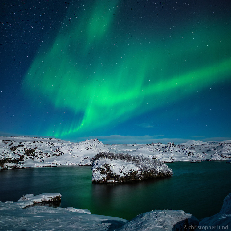 Northern lights dancing in moonlight over lake Mývatn, North Iceland.