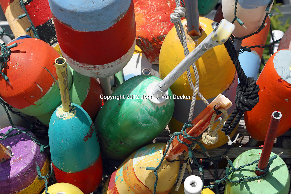 Colorful lobster trap markers grouped together as decoration near the Provincetown ferry. Privincetown, Cape Cod, Massachusetts, USA