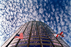Cirrocumulus clouds hover above the pink-mirrored facade of the state office building in Tampa, Florida.