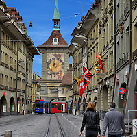 Marktgasse and Zytgloggeturm Clock Tower in Bern, Switzerland<br /> Marktgasse is the main pedestrian street through the old town of Bern.  It&rsquo;s flanked with 17th and 18th century buildings and arcades that are decorated with colorful flags, statues, fountains and guild signs.  Ahead of this couple is the 13th century Zytgloggeturm tower with the painted fresco called &ldquo;Beginning of Time&rdquo; on this west side and the famous astronomical clock facing Kramgasse.