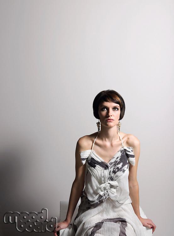 Woman in dress sitting in studio