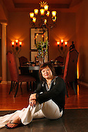 CAPTION: (Odessa 06/09/2006) (1 of 4) (PLEASE LEAVE WARM TONES IN BACKGROUND) Kathy Hsu (cq) sits by the formal dining room of her Odessa home. Warm lighting, a custom table and unique chairs add style to the room. Jay Tenuta of La Bella Interiors decorated the home with Hsu, his long-time design associate. SUMMARY: The My House next week is a beautiful one decorated by our friend Jay Tenuta of LaBella Interiors. It was for Kathy Hsu, the designer from Beijing and her family - all concert pianists.