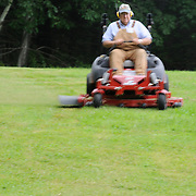 7/3/11 -- Rt 129 , Maine. Jim Bailey mows a section of grass. ..A stretch of the road not often traveled. Spanning communities, classes and styles ~ of farmers and fishermen, retired and plugging, the elite and working waterfront. (This area has huge potential for great photojournalism).  Photo by Roger S. Duncan.
