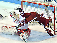 (BOSTON MA 030516)-U Mass' Austin Plevy goes airborne after his scoring attempt was stopped by Boston University's Sean Maguire. Herald photo Chris Christo
