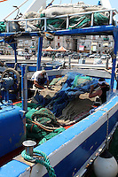 Pescatori a poppa sistemano le reti.