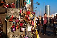 Europa, Deutschland, Koeln, Vorhaengeschloesser als Liebesschloesser (ital. Lucchetti d'Amore) am Zaun entlang des Fussweges der Hohenzollernbruecke ueber den Rhein. Die Schloesser mit Gravuren werden nach einem Brauch von Verliebten an Bruecken angebracht. Der Schluessel wird anschliessend in den Rhein geworfen, KoelnTriangle Tower.<br /> <br /> Europe, Germany, Cologne, padlocks on fence of footpath of the Hohenzollern railway bridge. Young couples seal their love with engraved padlocks and throw the key into the flowing river Rhine below, Cologne Triangle Tower.