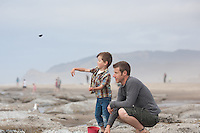 Oliver Whitehead throws rocks into the ocean with his father at Lincoln City beach, Oregon.  Tossing rocks.<br />