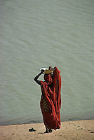 May 1978, Senegal --- Muslim Woman Standing on the Beach --- Image by © Owen Franken