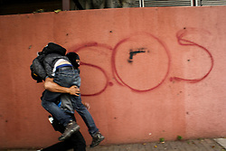 A demonstrator helps his comrade wounded by a tear gas bomb during a protest against Venezuelan President Nicolás Maduro in Caracas on May 3, 2017.