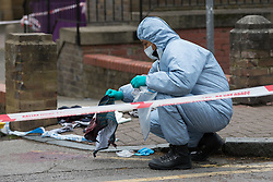 © Licensed to London News Pictures. 29/04/2017. London, UK. A forensic police officer gathers evidence at the crime scene cordon in Green Bank, Wapping, east London. At approximately 23.15 hours on Saturday 28th April Tower Hamlets police were called to an incident at Chancellor House, Green Bank, Wapping, E1W. A male in his mid twenties was discovered with knife wounds and was taken to the Royal London Hospital by London Ambulance Service. Photo credit: Vickie Flores/LNP