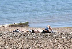 © Licensed to London News Pictures. 19/04/2020. Brighton, UK. People sunbathing on Brighton seafront at Brighton and Hove, during a pandemic outbreak of the Coronavirus COVID-19 disease.  Photo credit: Liz Pearce/LNP
