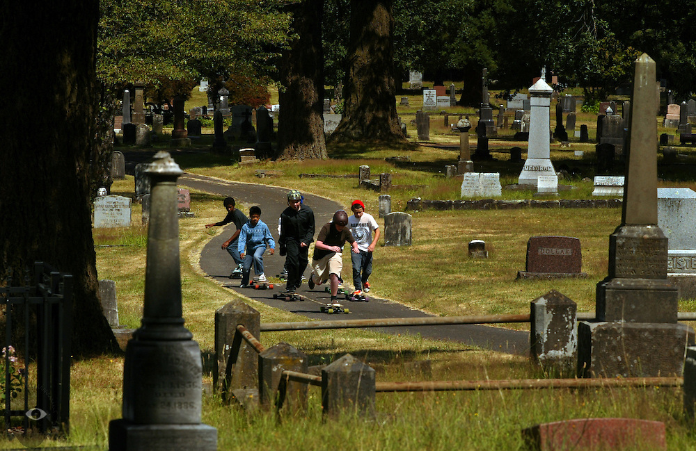 Young skateboarders ride through the St. John the Apostle Cemetery as a tribute to a friend during his funeral service, he died suddenly in his sleep from an undiagnosed heart ailment. As an avid skateboarder, friends were encouraged to bring their boards to the service though the tribute ride was a spontaneous gesture on their part.