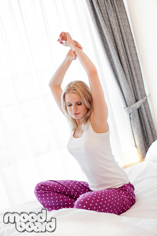 Beautiful young woman stretching on bed