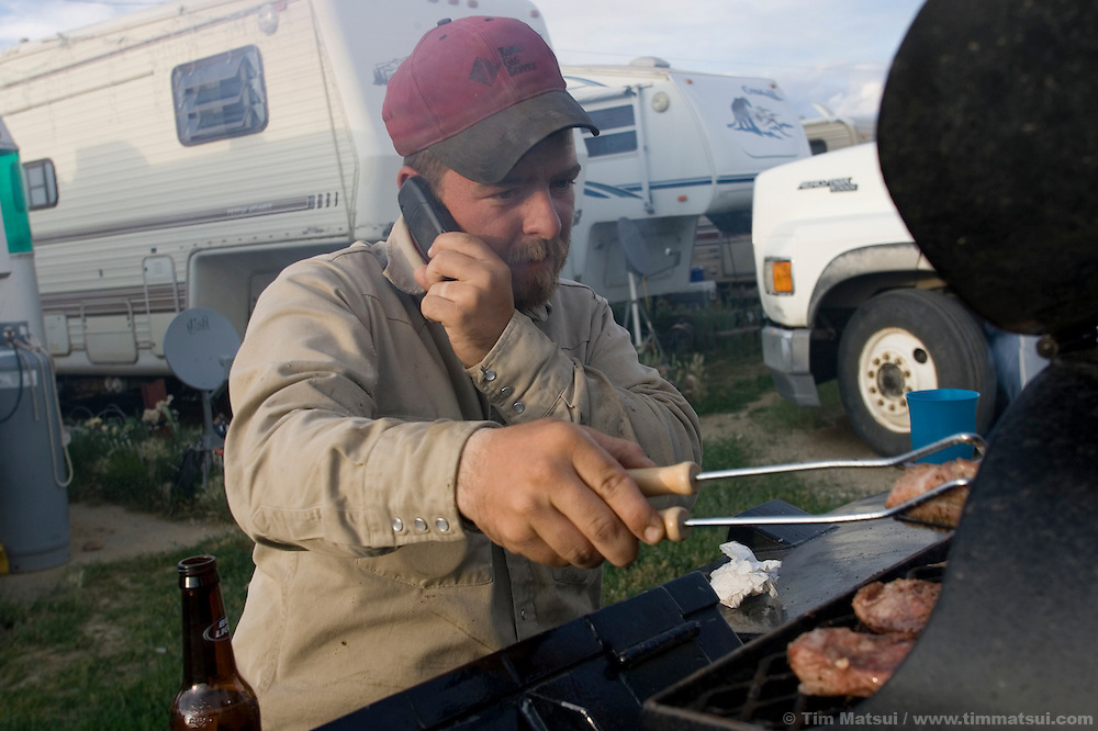 PINEDALE, WY - Welder Reed Helderman, of Oklahoma, bar-b-que's on his welding truck at the trailer park where he is living for several months in Pinedale, Wy., on August 10, 2005. Rental housing and hotel rooms are hard to find in Pinedale because the town of 1400 is suffering from the pressures of a natural gas boom with gas field workers and private contractors occupying many of the rooms available. New high density construction proposals are often met with public resistance in spite of a cry for denser, more affordable housing. Farms and ranches are being broken up and sold typically as two, five, 10, and 20 acre lots on septic systems and well water which will make it difficult to extend town utilities past a growing ring of private lots. One of the local sayings is that the escalating real estate prices are a result of the billionaires moving into nearby Jackson, WY, who are pushing out the millionaires who then move to Pinedale. According to realtor Travis Bing, anything one 'would want to buy' starts at about $200,000 with many homes selling for $450,000 and up. Realtor Cyd Goodrich believes there is a shortage of low to middle income homes. Pinedale currently has the lowest unemployment rate in the state and is experiencing another boom cycle both in real estate and in energy as natural gas production in two nearby gas fields ramps up for year-round production.