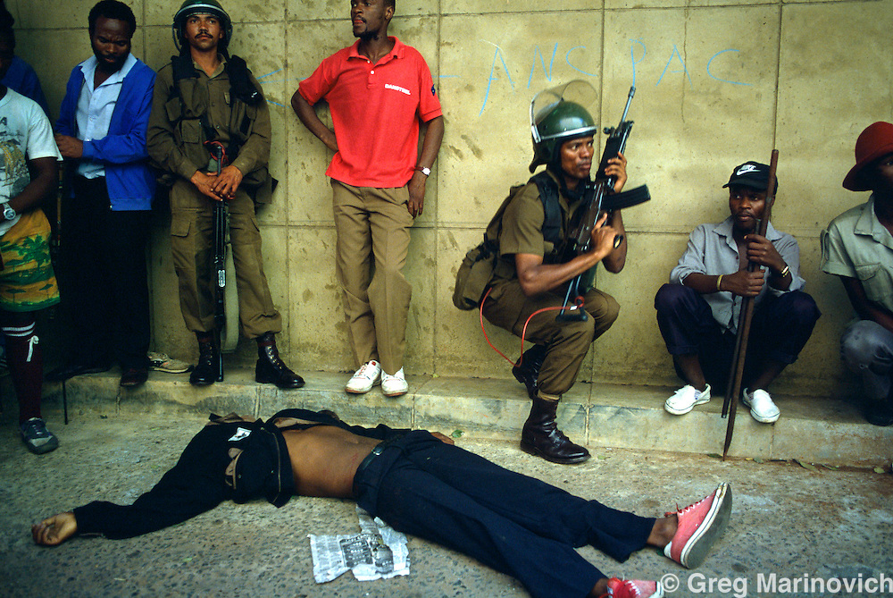 Johannesburg, South Africa, 1994. SADF soldiers and IFP members take cover under fire as unknown gunmen opened fire on Inkatha Freedom Party marchers at the Library Gardens, Johannesburg 1994. Many IFP supporters killed and wounded. Others were shot from the rooftops by persons unknown at the nearby Library Gardens. Johannesburg, South Africa