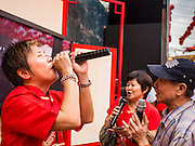 """19 FEBRUARY 2015 - BANGKOK, THAILAND: A woman sings karaoke on Yaowarat Road during Chinese New Year festivities in the Chinatown neighborhood of Bangkok. 2015 is the Year of Goat in the Chinese zodiac. The Goat is the eighth sign in Chinese astrology and """"8"""" is considered to be a lucky number. It symbolizes wisdom, fortune and prosperity. Ethnic Chinese make up nearly 15% of the Thai population. Chinese New Year (also called Tet or Lunar New Year) is widely celebrated in Thailand, especially in urban areas that have large Chinese populations.    PHOTO BY JACK KURTZ"""
