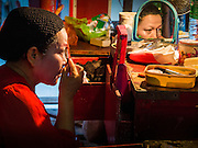 """30 JUNE 2016 - BANGKOK, THAILAND: A performer puts on her eye makeup before a Chinese opera performance at Chiao Eng Piao Shrine in Bangkok. Chinese opera was once very popular in Thailand, where it is called """"Ngiew."""" It is usually performed in the Teochew language. Millions of Chinese emigrated to Thailand (then Siam) in the 18th and 19th centuries and brought their culture with them. Recently the popularity of ngiew has faded as people turn to performances of opera on DVD or movies. There are about 30 Chinese opera troupes left in Bangkok and its environs. They are especially busy during Chinese New Year and Chinese holidays when they travel from Chinese temple to Chinese temple performing on stages they put up in streets near the temple, sometimes sleeping on hammocks they sling under their stage.       PHOTO BY JACK KURTZ"""