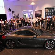 Porsche of Delaware Salesman Alex Witlon (left) removes a cover off the new 2014 Porsche Cayman S Thursday, May. 2, 2013, at Porsche of Delaware in Newark Delaware.