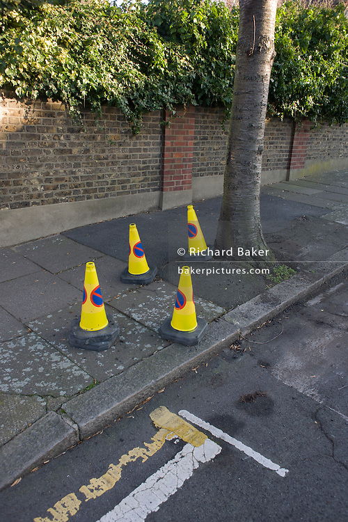 Four no parking to traffic cones gather on a residential south London street.