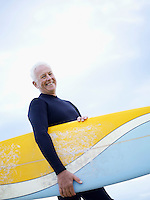 Senior man carrying surfboard smiling